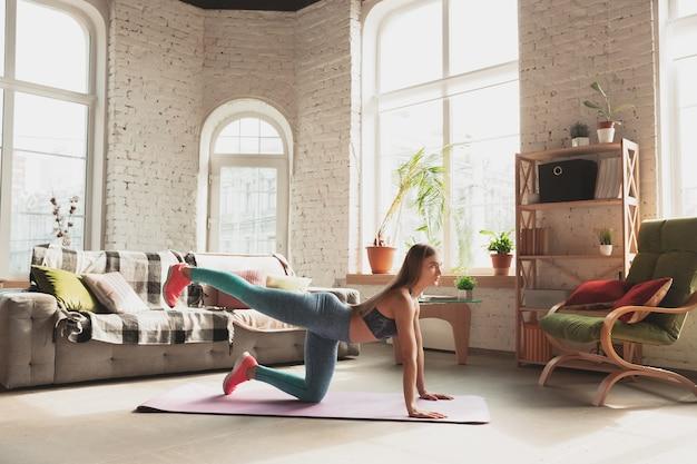 Giovane donna che insegna a casa corsi online di stile di vita sportivo aerobico fitness