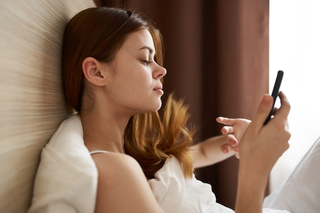 Adolescente della giovane donna con il telefono si trova a letto e le tende della finestra in background