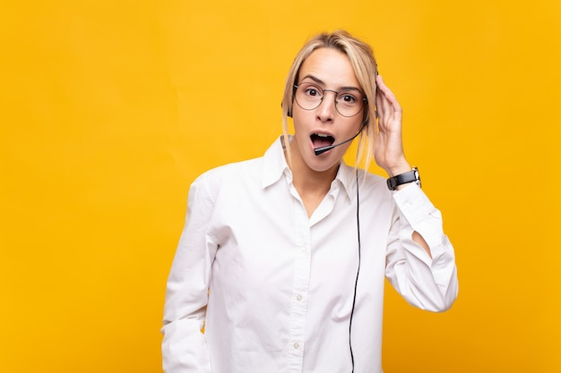 Operatore di telemarketing della giovane donna che sembra felice, stupito e sorpreso, sorridente e realizzando una buona notizia incredibile e incredibile