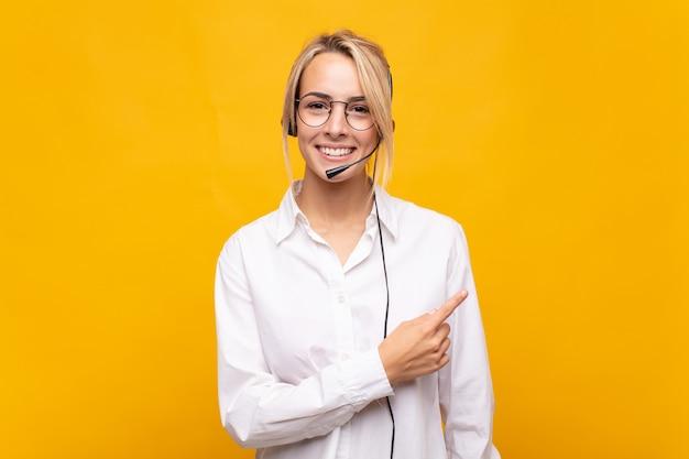 Telemarketer della giovane donna che sorride allegramente, sentendosi felice e indicando il lato e verso l'alto, mostrando l'oggetto nello spazio della copia