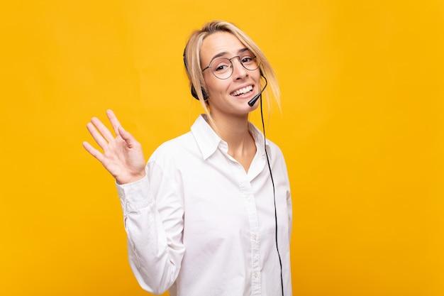 Giovane donna telemarketer che sorride felice e allegramente, agitando la mano, dandoti il benvenuto e salutandoti o salutandoti