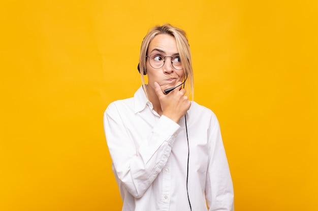 Giovane donna telemarketer pensando, sentendosi dubbiosa e confusa, con diverse opzioni, chiedendosi quale decisione prendere