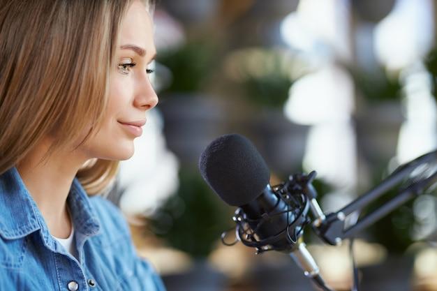 Giovane donna che dice alcune informazioni in linea nel microfono
