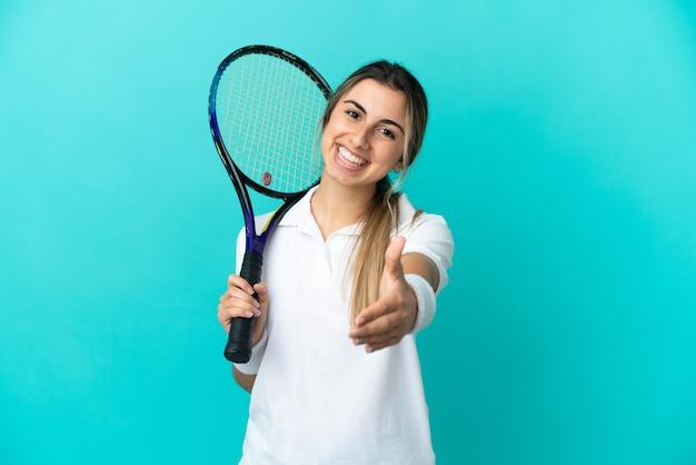 Giocatore di tennis della giovane donna isolato su priorità bassa blu che agitano le mani per la chiusura di un buon affare