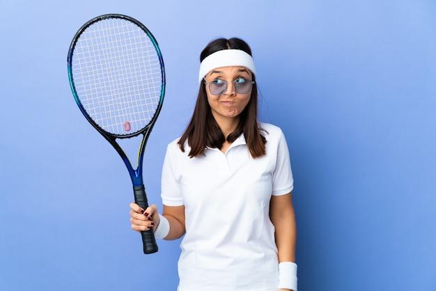 Tennis della giovane donna sopra isolato avendo dubbi mentre osservando in su
