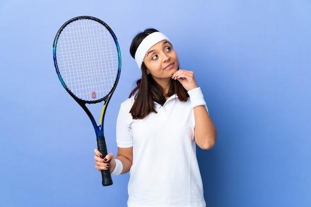 Tennis della giovane donna sopra isolato avendo dubbi