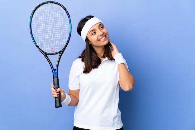 Tennis della giovane donna sopra isolato pensando un'idea