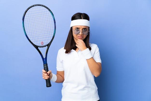 Tennis della giovane donna sopra la parete isolata che ha dubbi