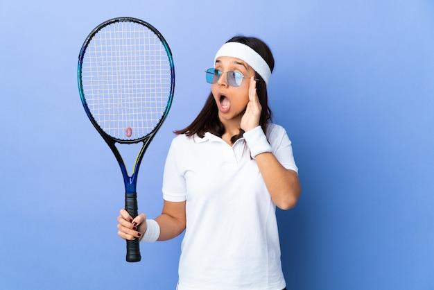 Tennis della giovane donna sopra la parete che bisbiglia qualcosa con il gesto di sorpresa mentre guardando al lato