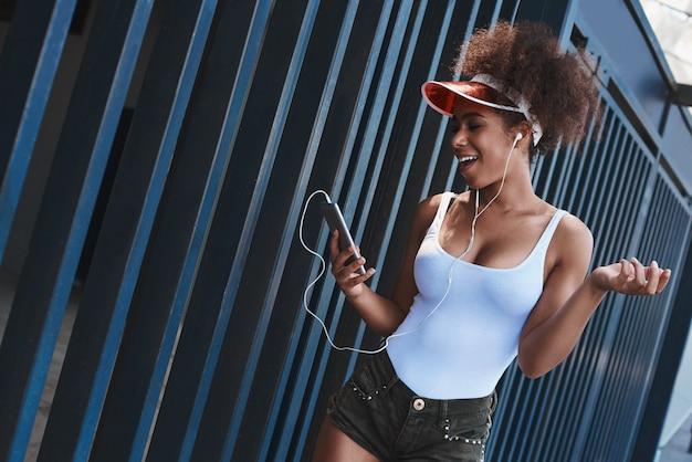 Giovane donna in visiera da tennis e auricolari stile libero sullo stre