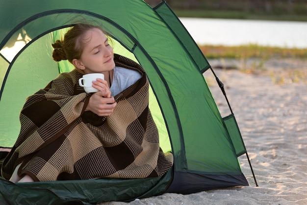 Giovane donna in tenda beve il tè del mattino