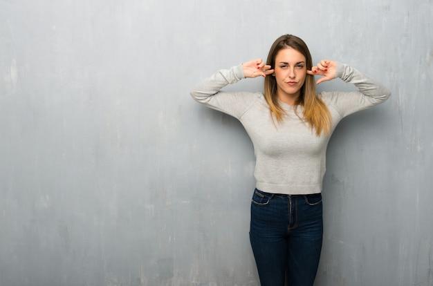 Giovane donna sulla parete strutturata che copre entrambe le orecchie con le mani