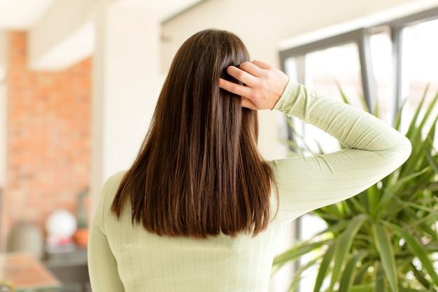 Giovane donna che pensa o dubita di graffiare la testa sentendosi perplessa e confusa indietro o vista posteriore