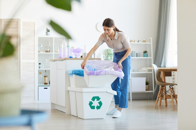 Giovane donna che getta la spazzatura che porta i bidoni in cucina