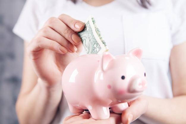 La giovane donna getta il dollaro nel salvadanaio