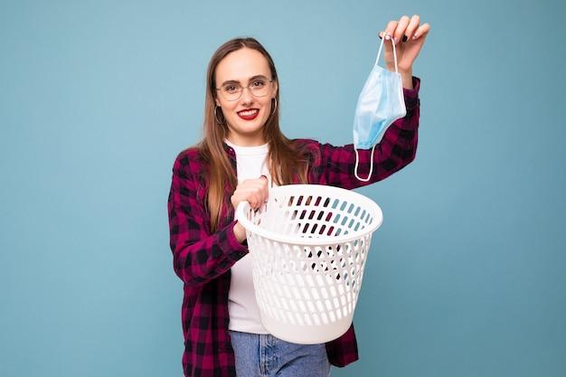 Una giovane donna getta una maschera protettiva usata nella spazzatura su sfondo blu