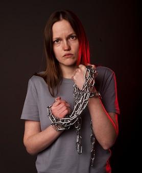 La giovane donna si lega con la catena, soffre di disperazione, problemi psicologici. persona infelice con il concetto di pesante fardello.