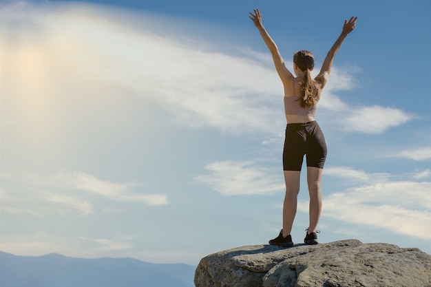 La giovane donna in cima alla montagna alzò le mani sullo sfondo del cielo blu.
