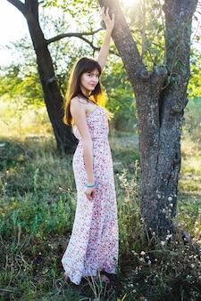 Giovane donna tocca il tronco d'albero in giardino, romanticismo estivo