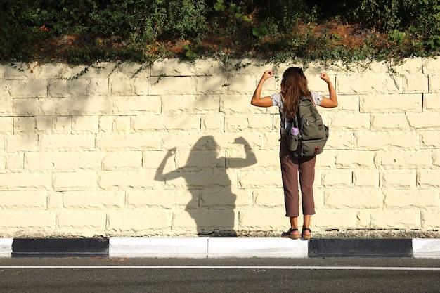 Giovane donna turiste sta con la schiena contro lo sfondo del muro di pietra chiara