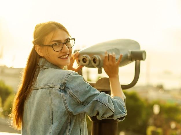 Turista di giovane donna in una giacca di jeans e occhiali guarda nel binocolo della città in città. concetto di viaggio