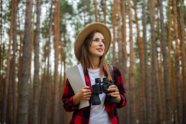 Turista della giovane donna in un cappello, camicia a quadri rossa tiene una mappa e un binocolo nella foresta.
