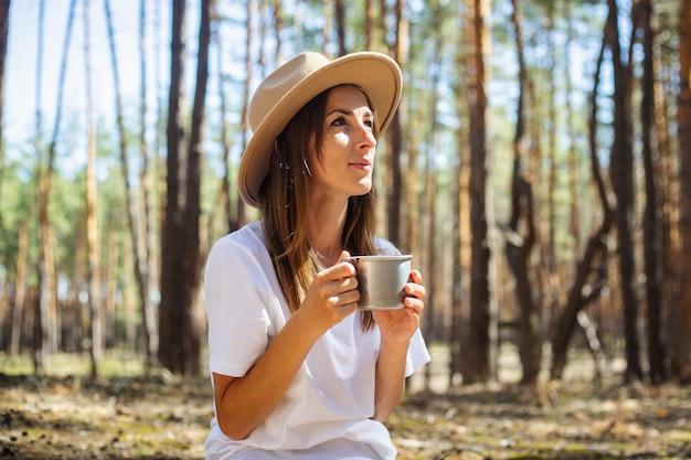 Turista della giovane donna in cappello e t-shirt beve tè o acqua durante una sosta nella foresta.