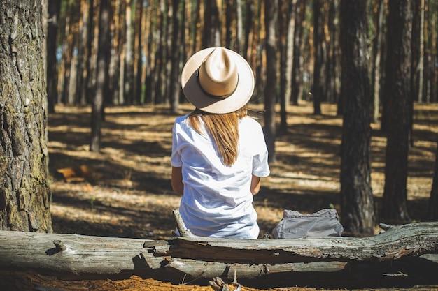 Turista della giovane donna in cappello e maglietta si siede su un registro durante una sosta nella foresta.