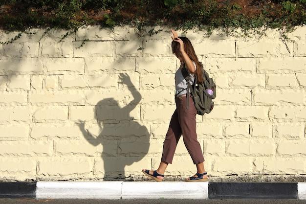 Il turista della giovane donna si diverte, gioca con l'ombra