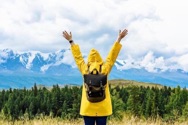 Turista della giovane donna in piedi con le braccia alzate con uno zaino