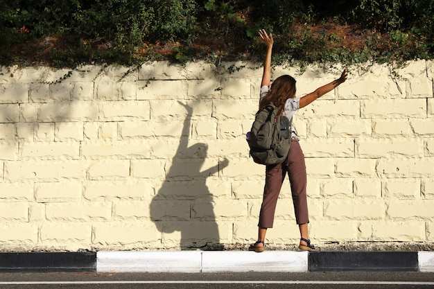 Turista della giovane donna sta con le spalle alla strada sul bordo del marciapiede e agitando le braccia