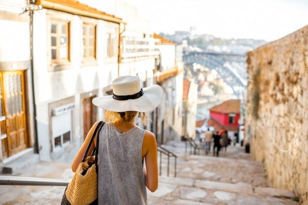 Turista della giovane donna che scende le scale con il famoso ponte di ferro sullo sfondo nella città di porto, portugal