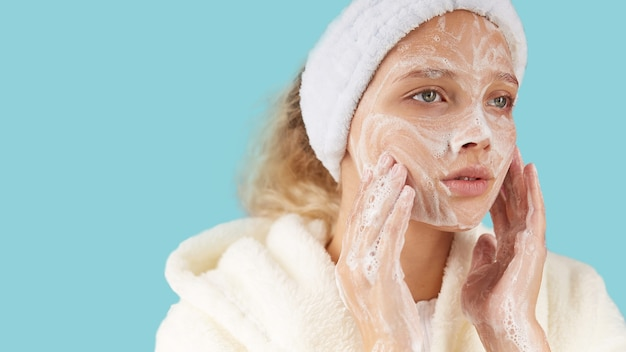Una giovane donna in un asciugamano applica la crema per il viso per pulire la pelle