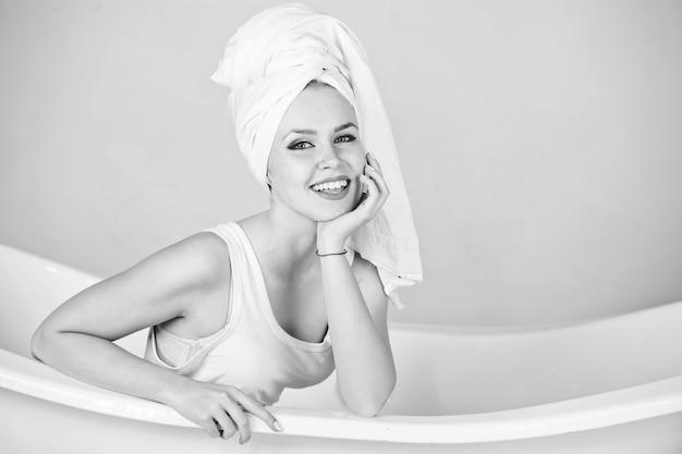 Giovane donna in asciugamano seduto nella vasca da bagno e sorridente. nero bianco.