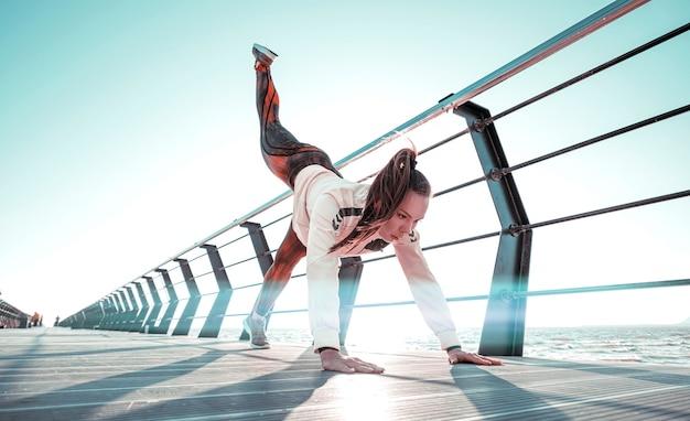Giovane donna in tuta sportiva esegue allenamento sportivo sul molo
