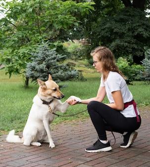 Giovane donna che addestra il suo cane in un parco