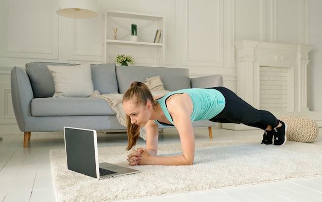 Una giovane donna che si allena online tramite il laptop. allenamento a distanza in casa durante la quarantena. ragazza che fa una plancia durante l'allenamento fitness. uno stile di vita sano.