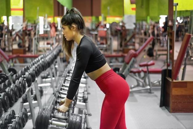 Giovane donna allenamento con manubri in palestra.