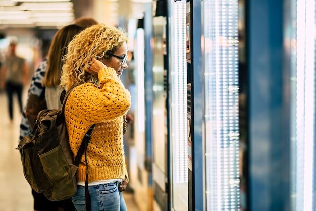 Concetto di viaggio della giovane donna al distributore automatico di cibo e bevande all'aeroporto