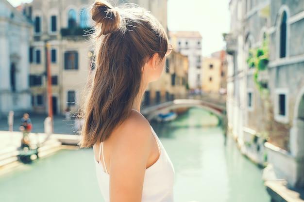 Giovane donna viaggia in italia ragazza gode di una splendida vista a venezia turista che cammina per le strade di venezia