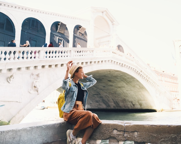 Giovane donna viaggia in italia vacanza in europa ragazza turista che cammina per le strade di venezia