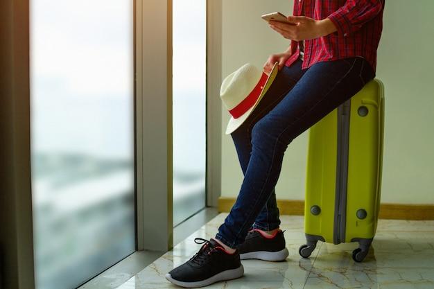 Viaggiatore di giovane donna in abiti casual con una valigia gialla