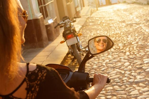 Viaggiatore della giovane donna alla guida di scooter per le strade della città vecchia
