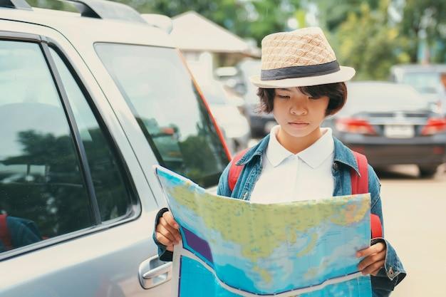 La tenuta della mano del viaggiatore della giovane donna e guarda la mappa al parco