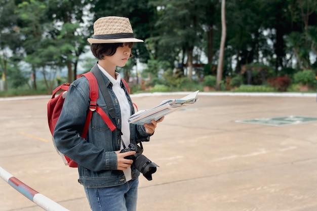 Mappa e macchina fotografica della tenuta della mano del viaggiatore della giovane donna al parco