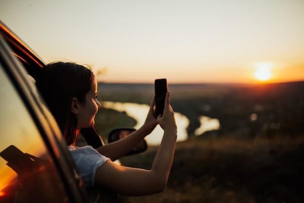 Viaggiatore di giovane donna all'interno dell'auto, guardando e scattare una foto bellissimo tramonto.