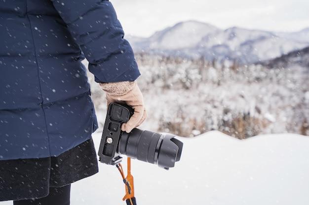Viaggiatore di giovane donna guardando il bellissimo paesaggio in inverno con la fotocamera
