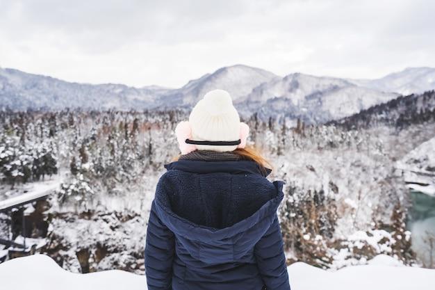 Viaggiatore di giovane donna guardando il bellissimo paesaggio in inverno