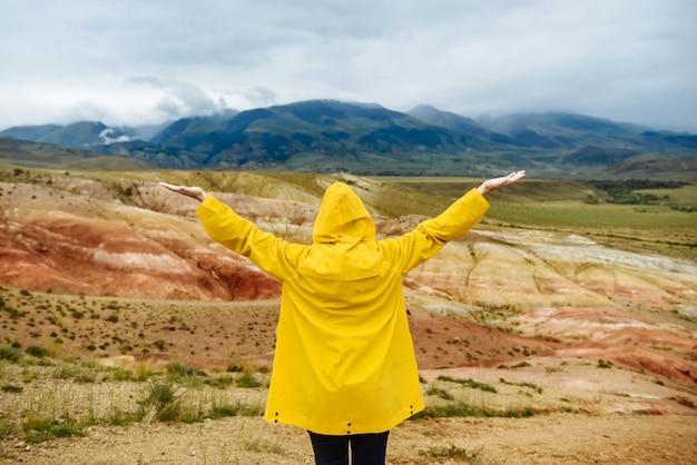 Viaggiatore della giovane donna guarda le montagne con le mani alzate