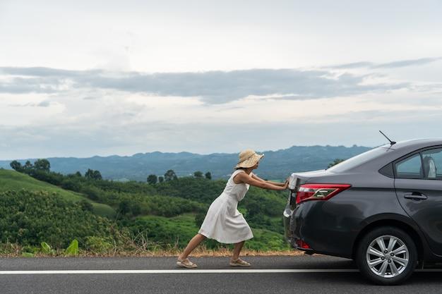 Viaggiatore della giovane donna che spinge un'automobile rotta lungo la strada
